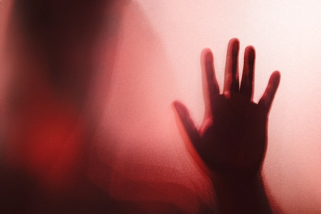 Sombra da mão fantasma por trás do vidro fosco