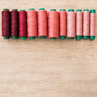 Sombra de bobinas vermelhas em fundo de madeira