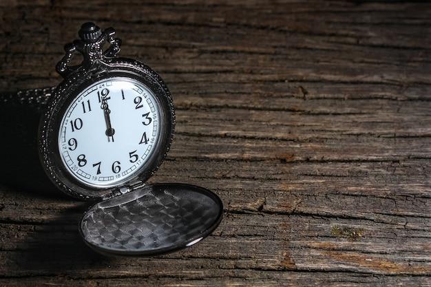 Sombra de claro e escuro do relógio de bolso preto vintage de luxo na mesa de madeira, abstrata para o conceito de tempo com espaço de cópia