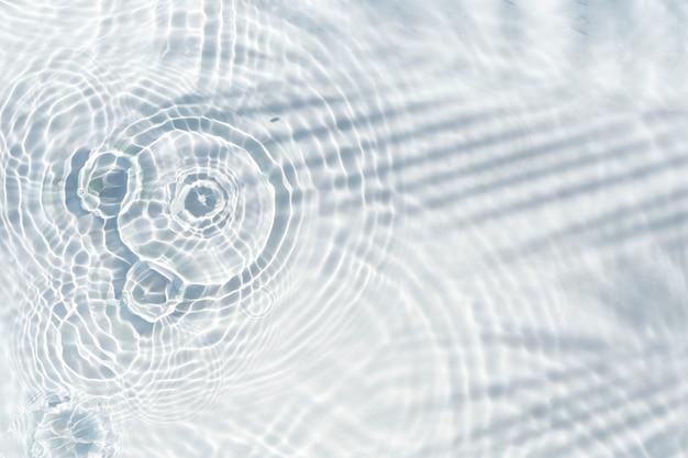 Sombra de folha de palmeira na água transparente e gotas de água caindo. vista superior, configuração plana.