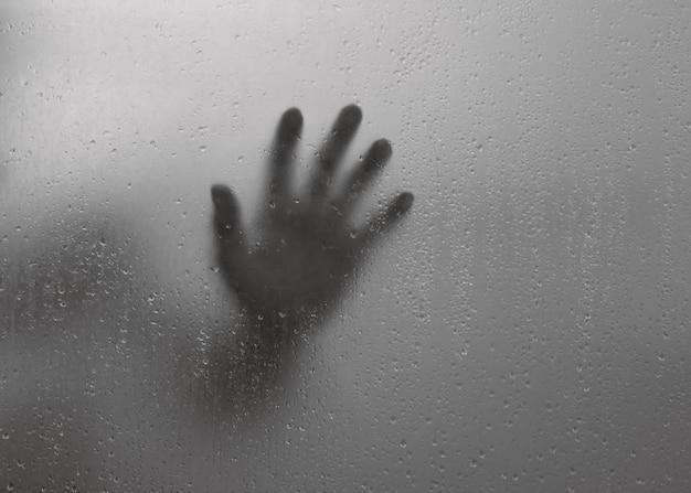 Sombra de mão embaçada por trás do espelho