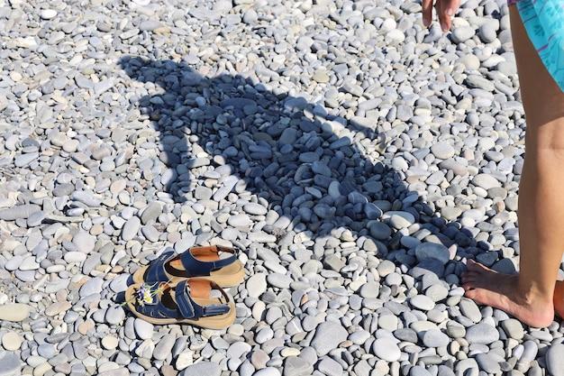 Sombra de mulher em pebble beach e sandálias na superfície em primeiro plano