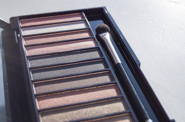Sombra de olhos em uma paleta de tons de marrom e nude com um pincel de maquiagem