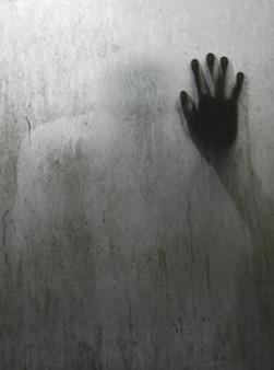 Sombra de pessoa mão atrás de espelho translúcido