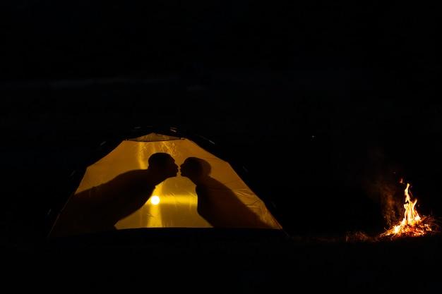 Sombra de um casal apaixonado beijos em uma barraca do turista na natureza.