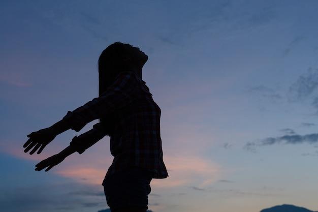 Sombra de uma mulher em pé e com a cabeça erguida, posando