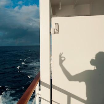 Sombra de uma pessoa gesticulando em um navio de cruzeiro silver shadow, mar da china oriental