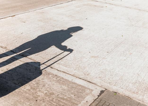Sombra de uma turista feminina segurando bagagem de rodas no asfalto