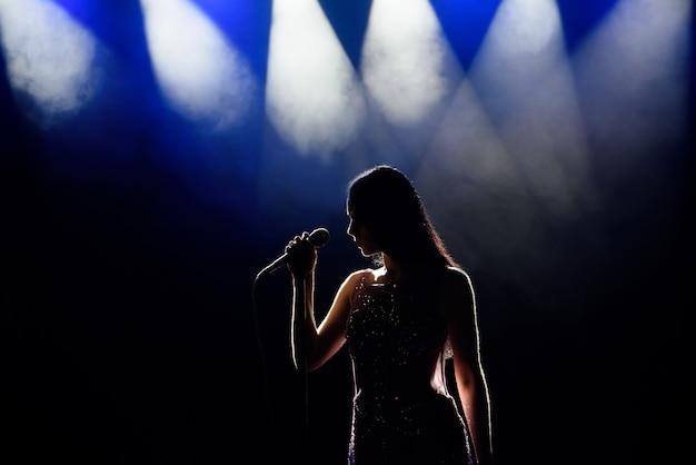 Sombra do cantor na luz no palco