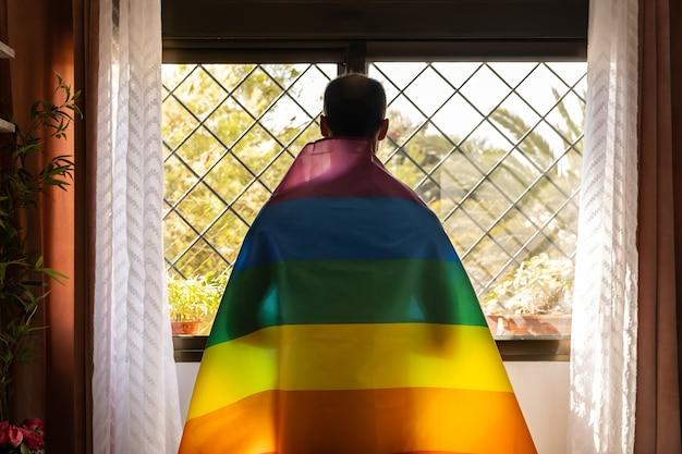 Sombra do homem através da bandeira lgbt segurando-a nos ombros e olhando pela janela ao ar livre