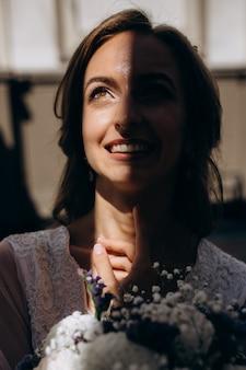 Sombra esconde metade do rosto da noiva enquanto ela sorri para o céu