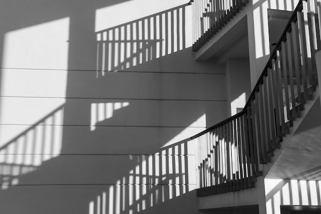 Sombras arquitetônicas. arquitetura de luz solar abstrato com sobreposição de sombra clara e preta da escada do edifício na parede de textura branca. processo de cor preto e branco.