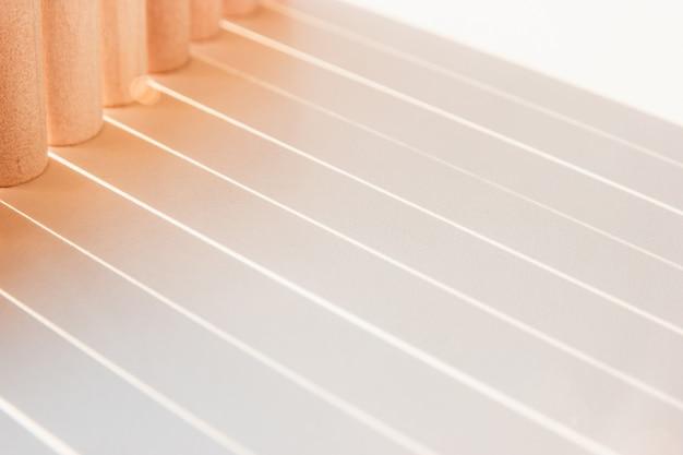 Sombras de linhas retas que fazem uma geometria iluminar uma superfície branca em uma cor ensolarada.