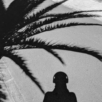 Sombras de palma e homem. vibrações tropicais mínimas