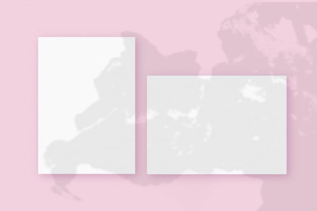 Sombras de plantas sobrepostas em uma folha horizontal e vertical de papel texturizado branco em um fundo de mesa rosa