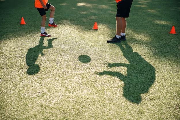 Sombras do treinador de futebol treina chutes com jovens jogadores de futebol.