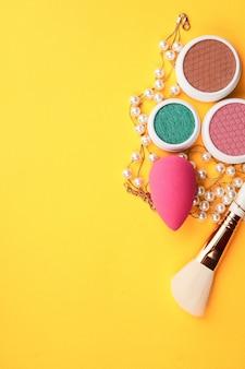 Sombras e pincéis de maquiagem em um amarelo