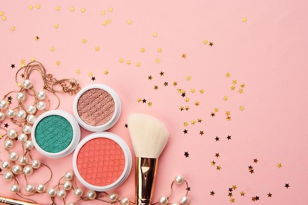 Sombras e pincéis de maquiagem em um rosa