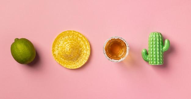 Sombrero, limão, tequila e cacto em fundo rosa.