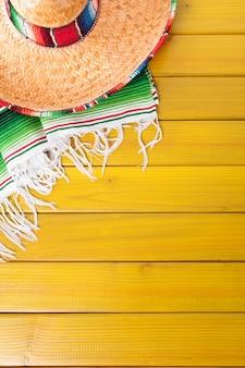 Sombrero mexicano e cobertor tradicional poncho colocado sobre um piso de madeira de pinho amarelo pintado
