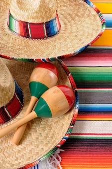 Sombreros mexicanos com maracas e mantas tradicionais do serape.