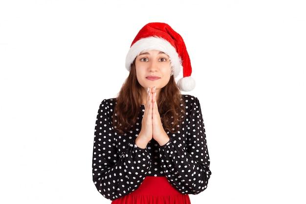 Sombria mulher bonita e tímida no vestido de mãos dadas em rezar, pedindo desculpas ou ajuda. garota emocional no chapéu de natal papai noel