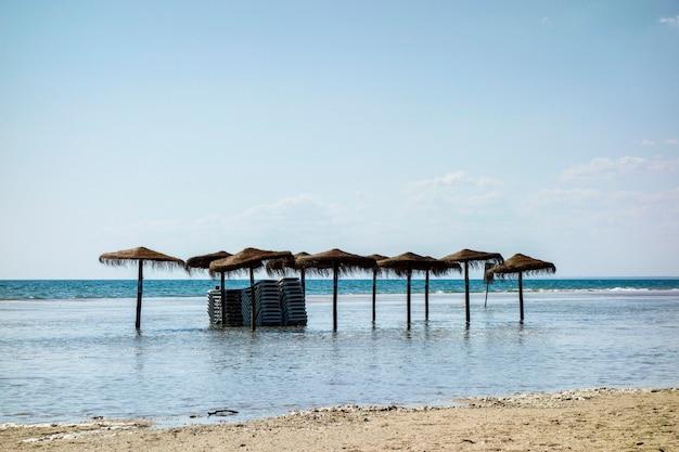 Sombrillas de cama na praia inundadas pela subida do mar