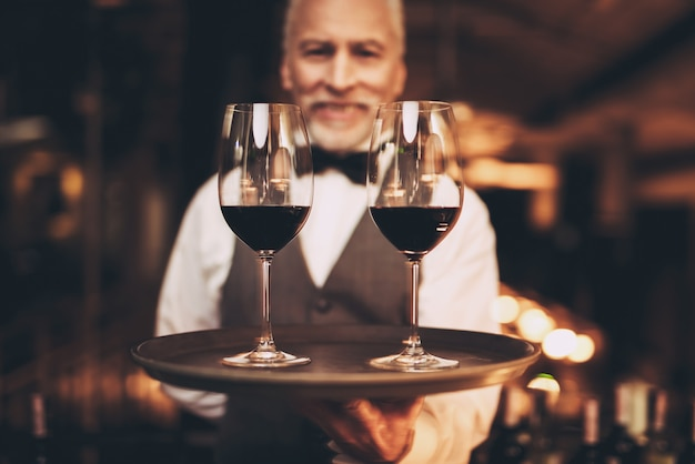 Sommelier com gravata borboleta detém bandeja com copos de vinho.
