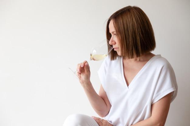 Sommelier de menina morena caucasiana segurando um copo de vinho branco
