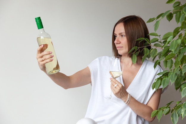 Sommelier de menina morena caucasiana segurando uma taça de vinho branco