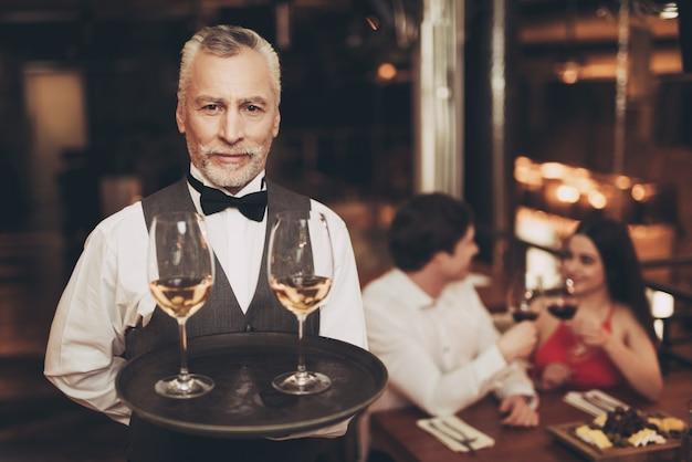 Sommelier está segurando a bandeja com copos de vinho branco.