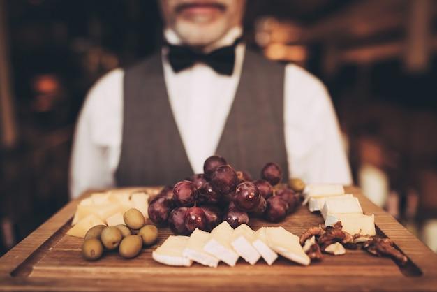 Sommelier está segurando a bandeja com lanches para vinho.