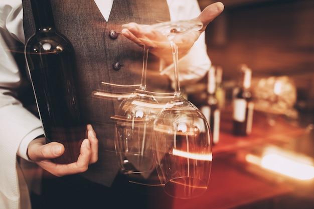 Sommelier na gravata borboleta está segurando com garrafa e copos