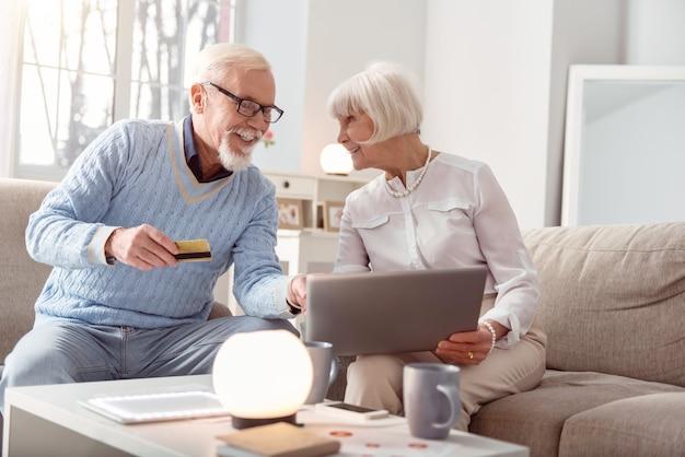 Somos viciados em compras. casal de idosos otimistas fazendo compras online juntos e o homem apontando para o laptop, escolhendo o item a ser comprado, enquanto dá seu cartão do banco para pagar por ele