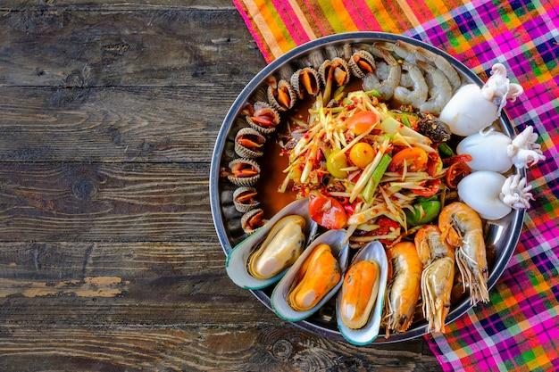 Somtum frutos do mar, com cascas de camarão, colocado em uma bandeja, lindamente colocado sobre uma mesa de madeira
