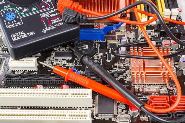 Sondas com multímetro digital na superfície da placa-mãe