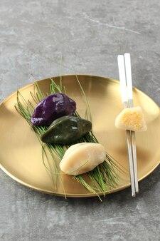 Songpyeon é um alimento tradicional coreano consumido durante o dia de ano novo ou no dia coreano de agradecimento. servido em prato coreano dourado com pauzinho. copiar espaço