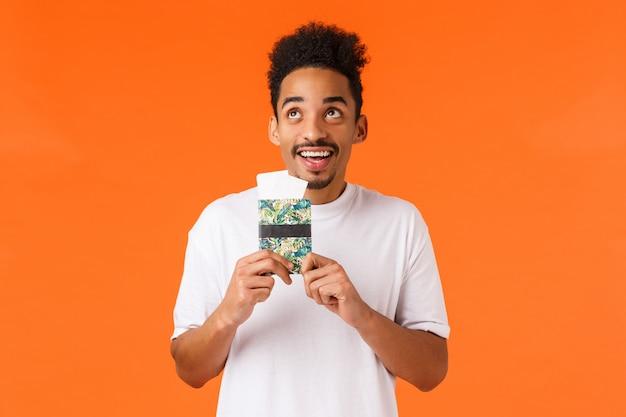 Sonhador alegre, sorrindo cara afro-americana com bigode, corte de cabelo afro, segurando o passaporte