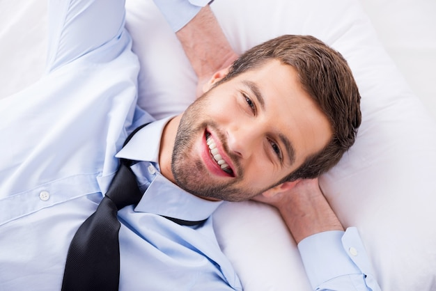 Sonhador de dia feliz. vista superior de um jovem bonito de camisa e gravata, segurando as mãos atrás da cabeça e sorrindo enquanto está deitado na cama