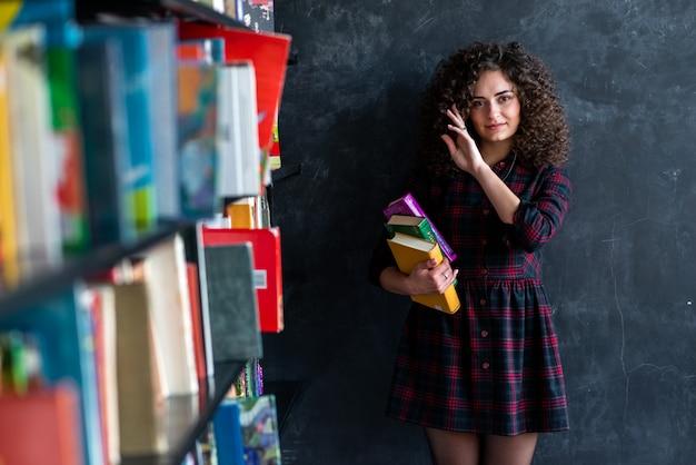 Sonhador encaracolado menina morena com um livro nas mãos de pé na biblioteca perto da parede cinza, tocando o cabelo