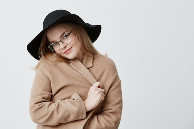Sonhador satisfeito fêmea jovem positiva no casaco retrô e chapéu, vestindo óculos elegantes, envolve o casaco, carrinhos, parece com satisfação. emoções humanas positivas