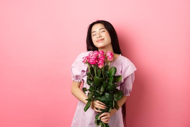 Sonhadora adolescente asiática se sentindo romântica, segurando flores e sonhando, imaginando o dia dos namorados, usando um vestido bonito, de pé no fundo rosa.