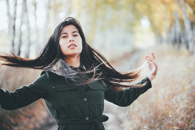Sonhadora garota bonita com cabelo preto longo natural sobre fundo de bokeh de outono amarelo folhas.