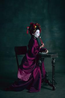 Sonhadora. jovem mulher japonesa como gueixa isolada na parede verde escura. estilo retro, comparação do conceito de eras. bela modelo feminina como personagem histórica brilhante, antiquada.