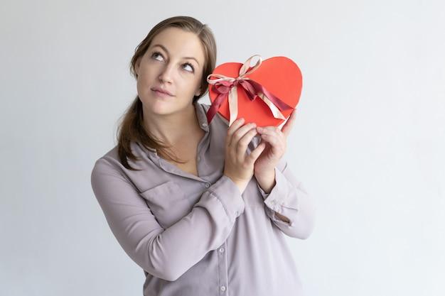 Sonhadora mulher bonita segurando coração vermelho em forma de caixa de presente