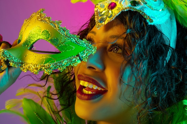 Sonhadora. mulher jovem e bonita no carnaval, elegante traje de máscaras com penas dançando na parede gradiente em neon. conceito de celebração de feriados, tempo festivo, dança, festa, diversão.