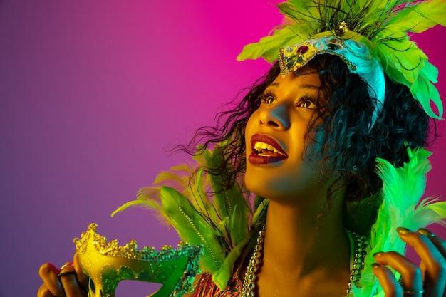 Sonhadora. mulher jovem e bonita no carnaval, elegante traje de máscaras com penas dançando no fundo gradiente em neon. conceito de celebração de feriados, tempo festivo, dança, festa, diversão.