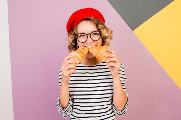 Sonhadora senhora bonita na boina vermelha segurando grandes croissants saborosos nas mãos.