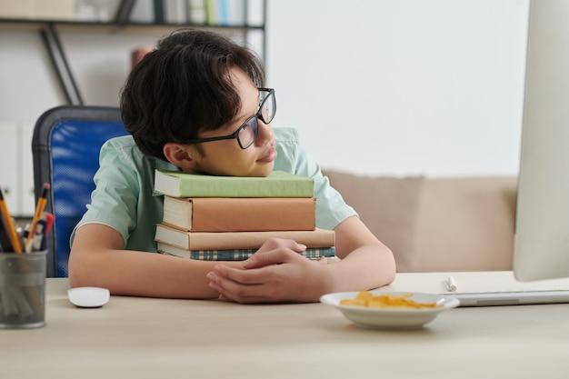 Sonhando com um estudante adolescente de óculos encostado na pilha de livros de alunos em sua mesa em casa