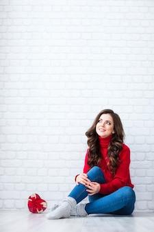 Sonhando com uma mulher bonita. jovem com caixa de presente em forma de coração vermelha em casa.